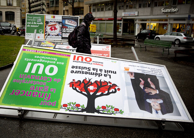 A man passes by election posters demanding a stop to immigration, in Geneva on Monday.