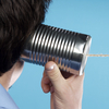 A man listens to a tin can telephone.