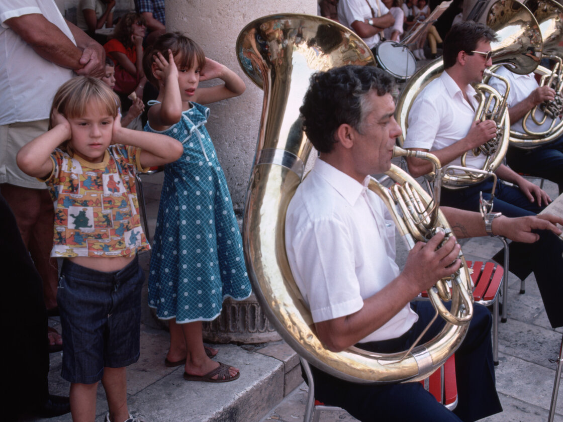 September 1984, Dubrovnik, Croatia --- Small children cover their ears as they stand next to a sousaphone player during a concert played by the Dubrovnik Saturday Band in Dubrovnik, Croatia, Socialist Federal Republic of Yugoslavia.