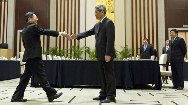Wang Yu-chi, head of Taiwan's Mainland Affairs Council, left, shakes hands with Zhang Zhijun, director of China's Taiwan Affairs Office, before their meeting in Nanjing, China, on Tuesday.