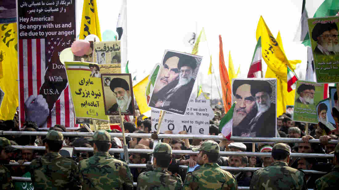 Iranians hold pictures of Iran's current supreme leader, Ayatollah Ali Khamenei, during the 35th anniversary of the 1979 Islamic Revolution in Tehran, Iran, on Tuesday.