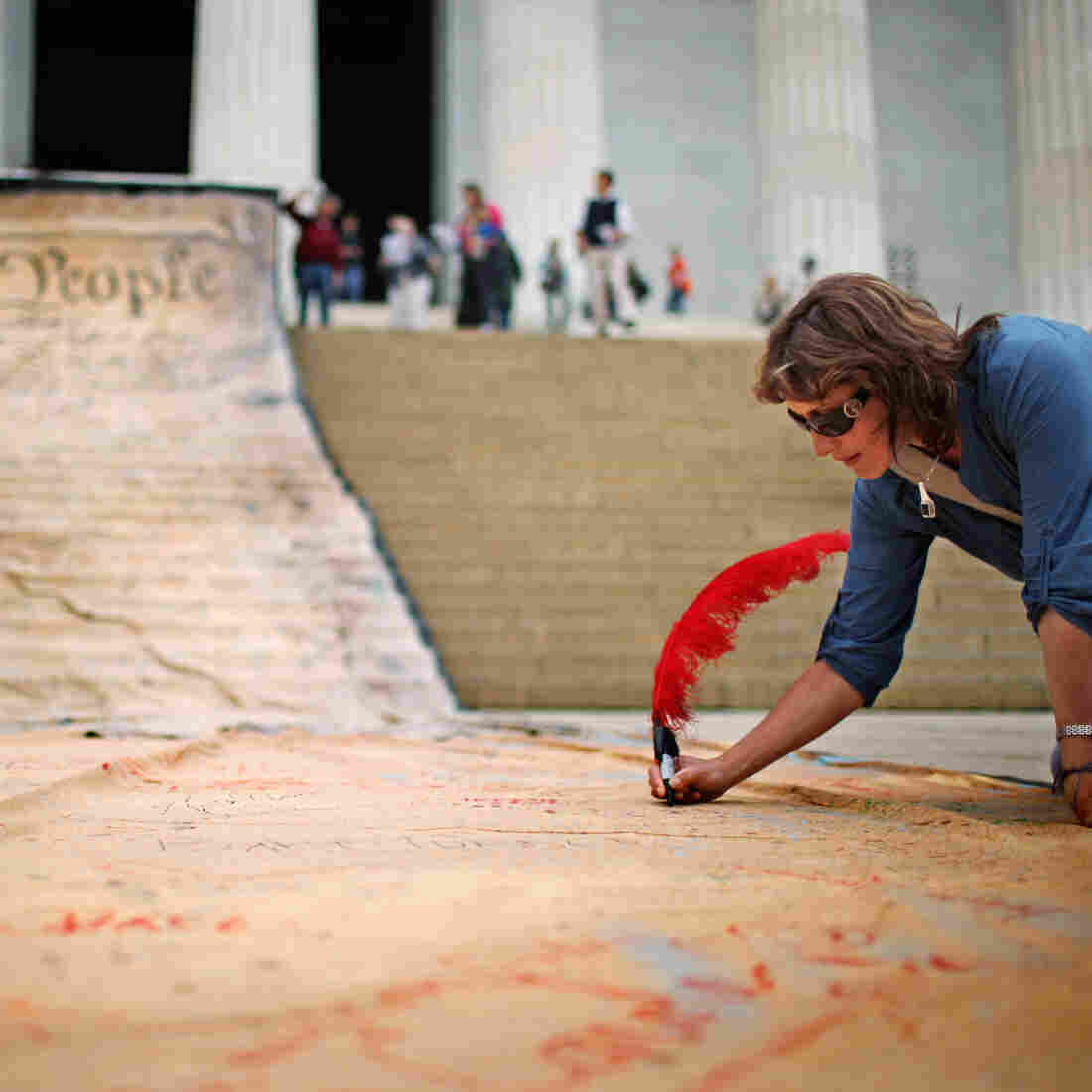 A woman signs a giant banner printed with the preamble to the U.S. Constitution during a demonstration against the Citizens United ruling in Washington in October 2010.