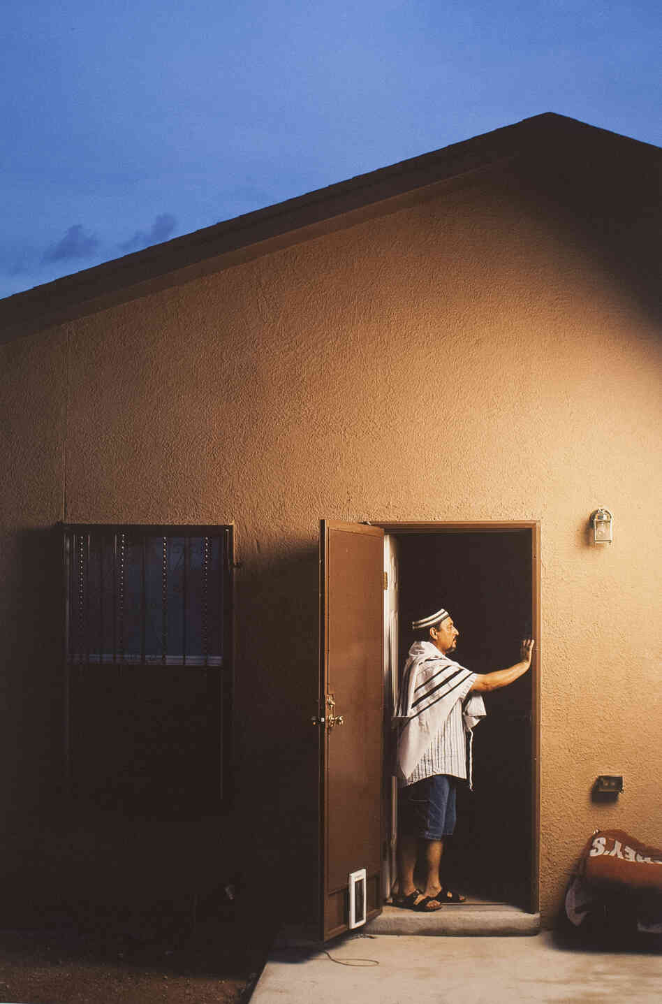 A man touches the mezuzah on his home in East El Paso, Texas.