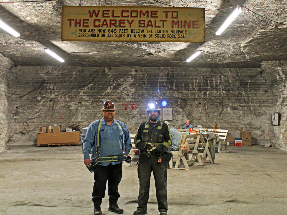 At Hutchinson Salt Co., John Kinkaid and Eric Price stand under the sign bearing the old name of the mine. (KCUR)