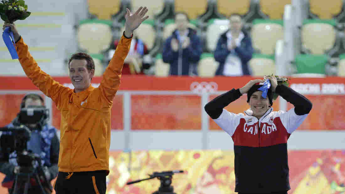 Silver medalist Denny Morrison of Canada celebrates his feat, made possible after a teammate gave him a slot in Wednesday's 1,000-meter speedskating race in Sochi. Morrison stands next to gold medalist Stefan Groothuis of the Netherlands.