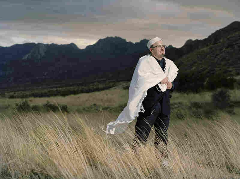 Daniel Diaz-Huerta dons his tallit, or prayer shawl, in front of the Organ Mountain near Las Cruces, N.M.