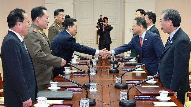 In this handout image provided by the South Korean Unification Ministry, Kim Kyou-Hyun (right) the head of South Korea's high-level delegation, shakes hands with his North Korean counterpart Won Tong-Yon before their meeting Wednesday in Panmunjom, South Korea.