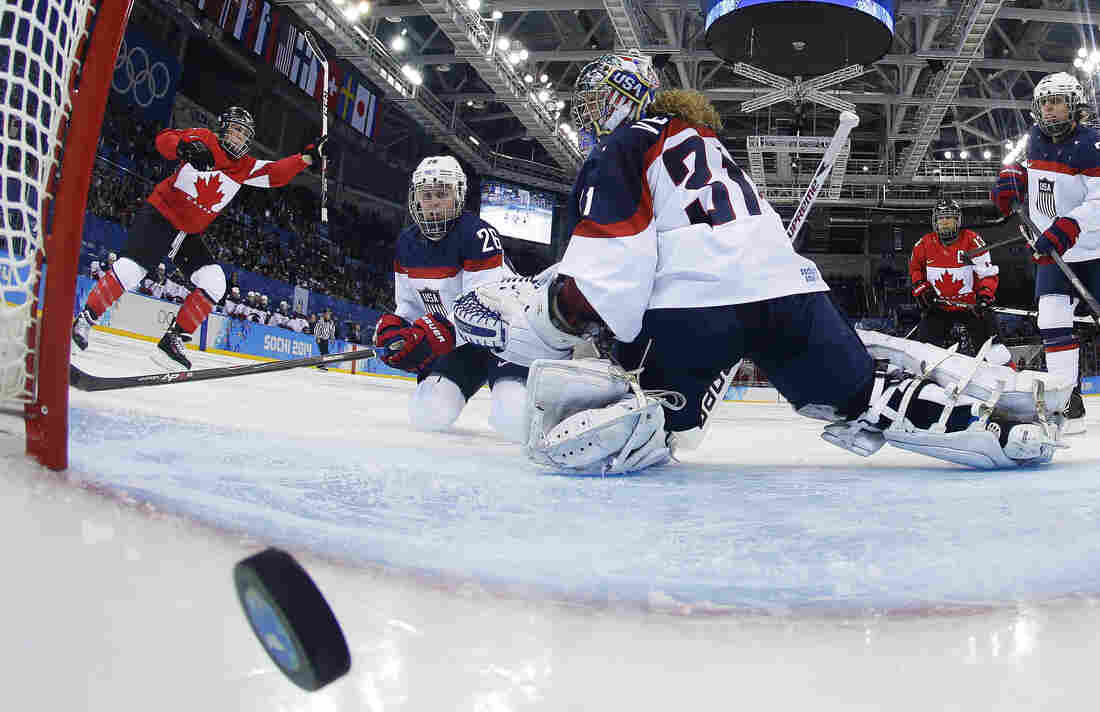 Goalkeeper Jessie Vetter and Kendall Coyne (26) of the United States look back at the puck as Meghan Agosta-Marciano of Canada celebrates her goal in Sochi on Wednesday. Canada defeated the United States, 3-2.