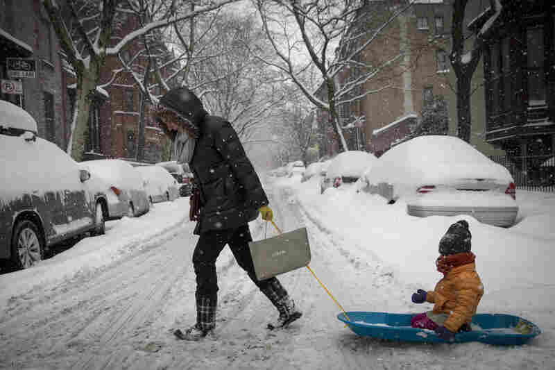 A woman pulls her child in a sled through the
