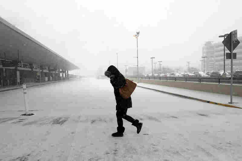 A pedestrian braces against the wind and snow on her way into Raleigh-Durham International Airport on Thursday in Morrisville, N.C. Flights were canceled across the region because of weather.