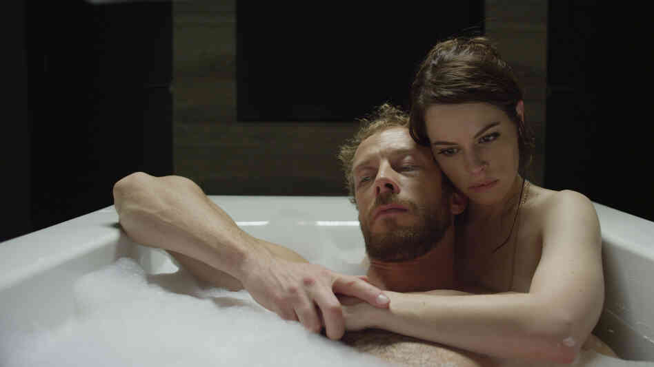 Kate (Emily Hampshire) treats the victims of zombie attacks — among them her husband, Alex (Kris Holden-