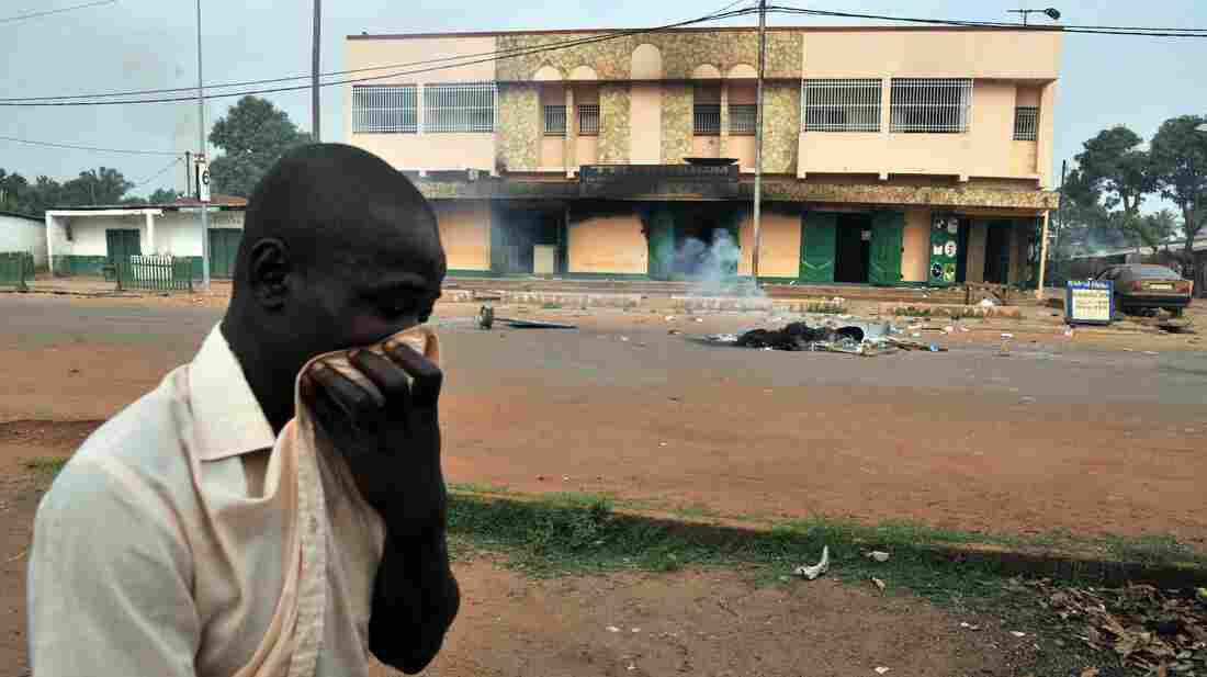 A man covers his nose as he walks past a charred body on Feb. 9 in central Bangui.
