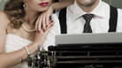 A man and a woman at a typewriter.