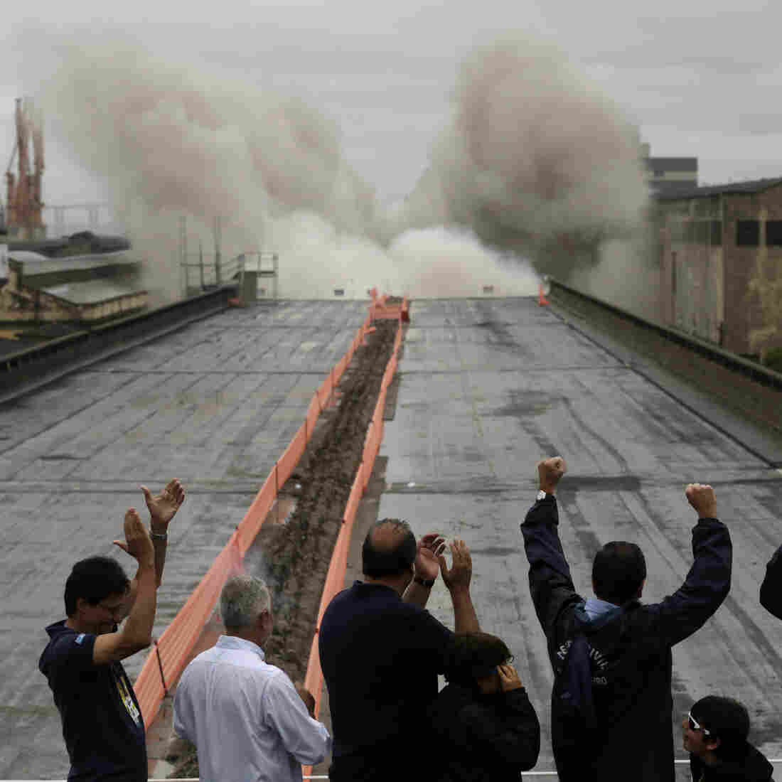 Local authorities celebrate a demolition explosion that's part of Rio's Porto Maravilha urbanization project, in Rio de Janeiro, on Nov. 24, 2013. The state- and federal-supported project is part of the city's redevelopment ahead of the 2016 Summer Olympic Games.