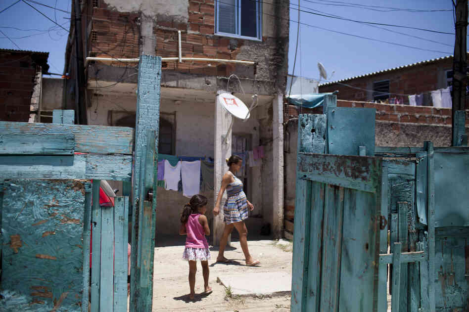Maria Victoria Agostinho, 5, walks outside her home in the Vila Autodromo area of Rio. Her family is slated for eviction, along with others in the area, to make way for building projects related to the 2016 Summer Olympics.