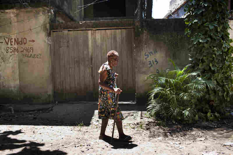 An elderly woman walks past a home that is marked for eviction in the favela community of Vila Autodromo.