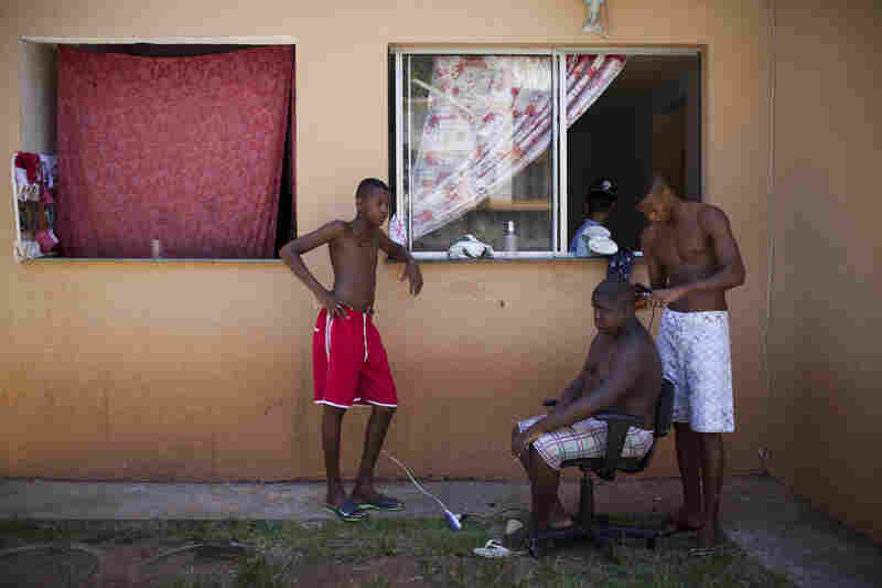 Residents hang out in front of their apartment, in Rio de Janeiro's far west zone of Campo Grande. Many families relocated to this area three years ago to make way for Olympic building.