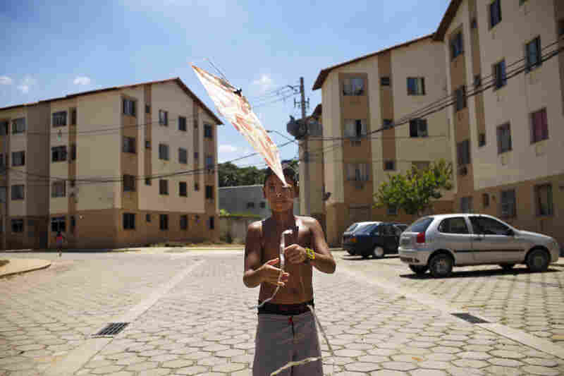 A resident plays with a kite in the Oiti apartment complex, in Rio de Janeiro's far west zone of Campo Grande. Many families were relocated here three years ago from another part of Rio.