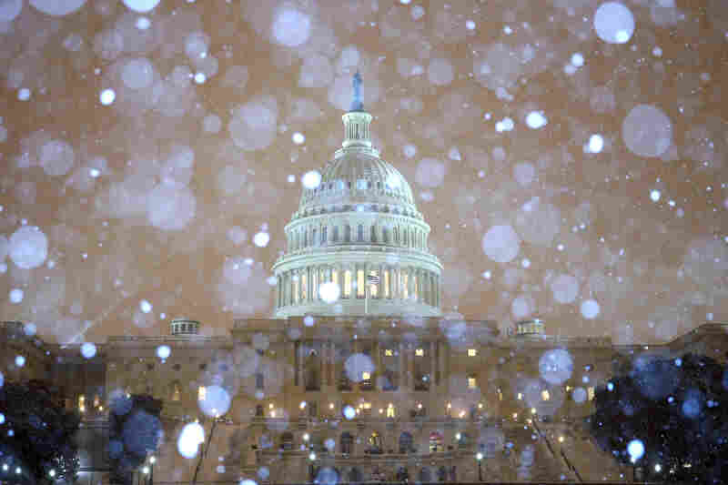 Snow falls in front of the U.S. Capitol building. The federal government's offices are closed Thursday, and more than 6,000 flights within the U.S. have been canceled.