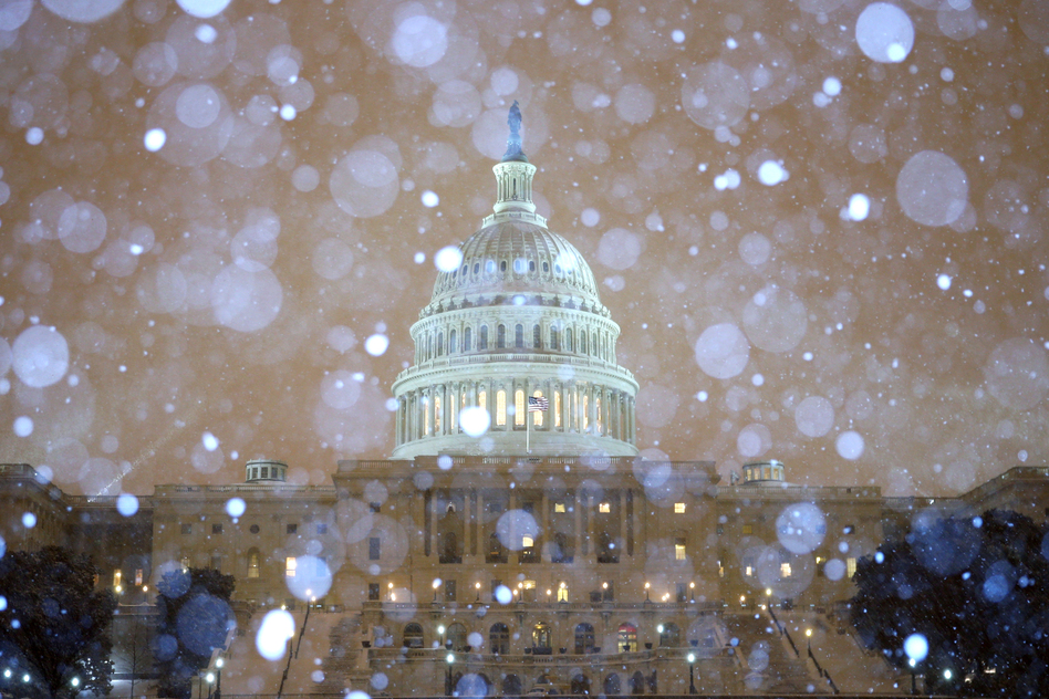 Snow falls in front of the U.S. Capitol building. The federal government's offices are closed Thursday, and more than 6,000 flights within the U.S. have been canceled. (Getty Images)