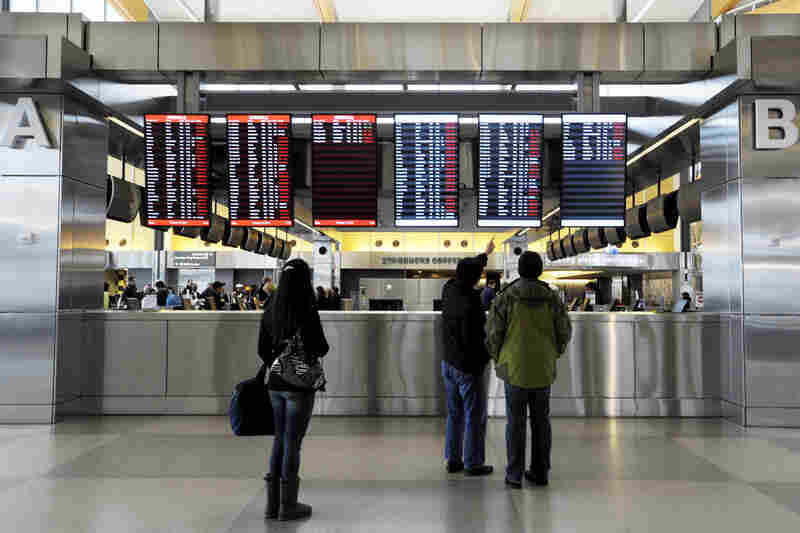 Travelers at Raleigh-Durham International Airport check on canceled departures, displayed in red, on Wednesday in Morrisville, N.C. More than 100 flights were canceled by 2 p.m. because of the winter storm hitting the area.