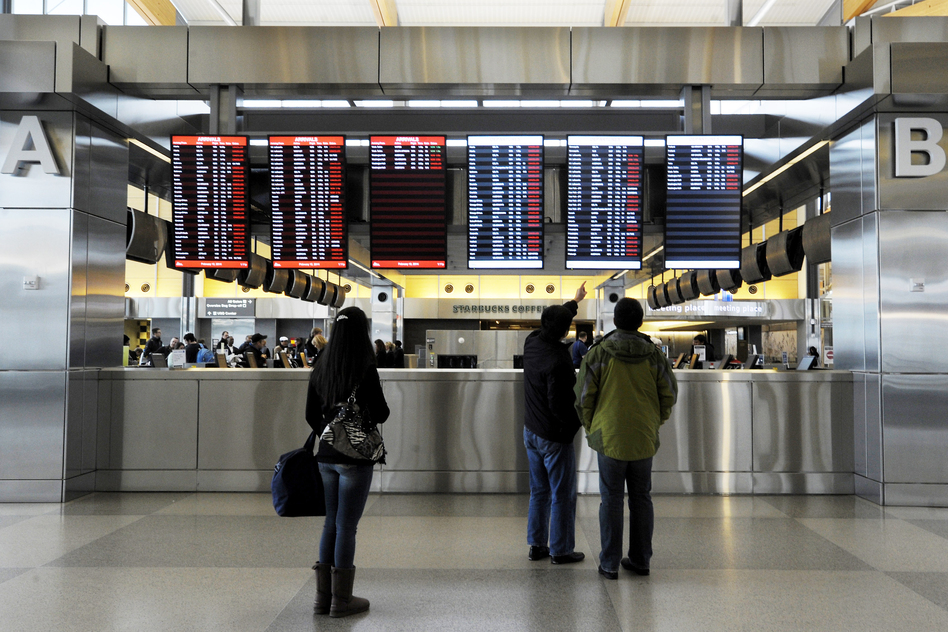 Travelers at Raleigh-Durham International Airport check on canceled departures, displayed in red, on Wednesday in Morrisville, N.C. More than 100 flights were canceled by 2 p.m. because of the winter storm hitting the area. (Getty Images)