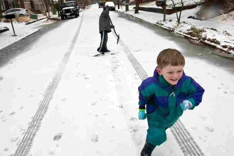 Milo Kortemeier runs away from John Staton after pelting him with a snowball in Decatur, Ga. Icy road conditions caused some businesses and schools to shut down in the greater metro Atlanta region.