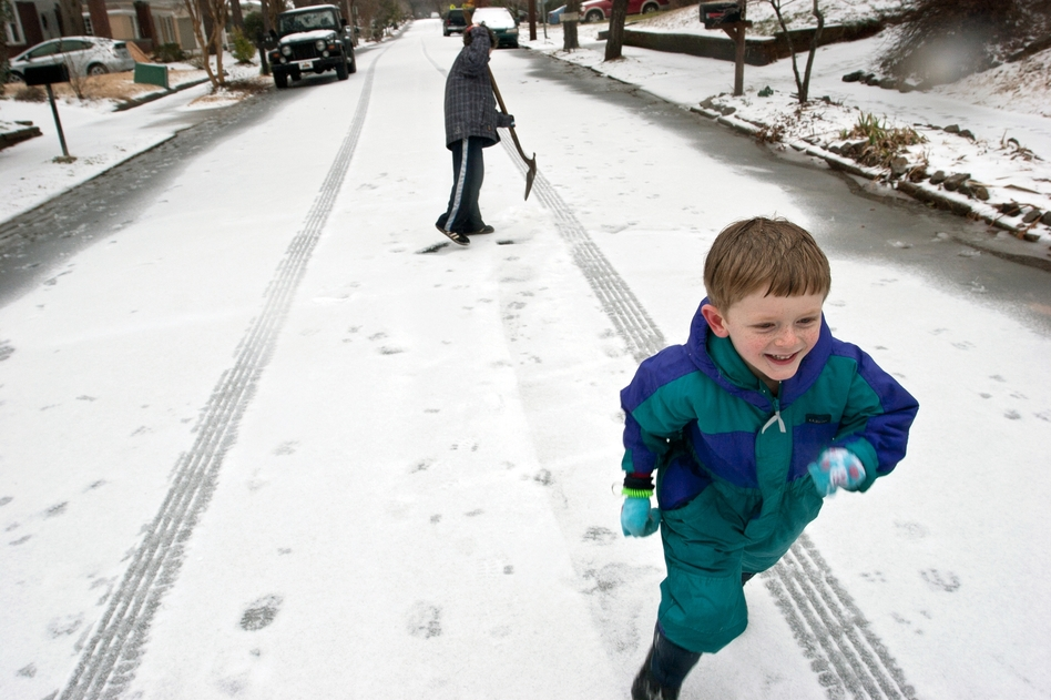 Milo Kortemeier runs away from John Staton after pelting him with a snowball in Decatur, Ga. Icy road conditions caused some businesses and schools to shut down in the greater metro Atlanta region. (AP)