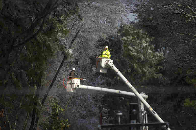 Multiple crews work to restore power after a winter storm brought down lines and continues to blow transformers in Fairburn, Ga. As crews worked to restore power to hundreds of thousands of Georgians, forecasters hoped warmer temperatures Thursday and a few rays of sunshine would melt ice-coated roads across the state.