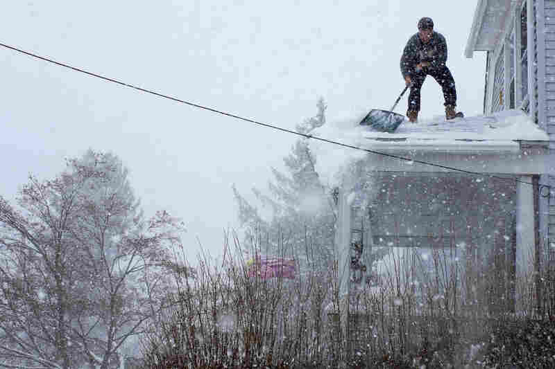 """Chris Starace works to clear snow from his home's roof in Ossining, N.Y. According to the National Weather Service, """"a wide swath of heavy snow accumulations are expected with this storm"""" Thursday and Friday from Maryland through Pennsylvania and New York and then on to Massachusetts and farther north."""
