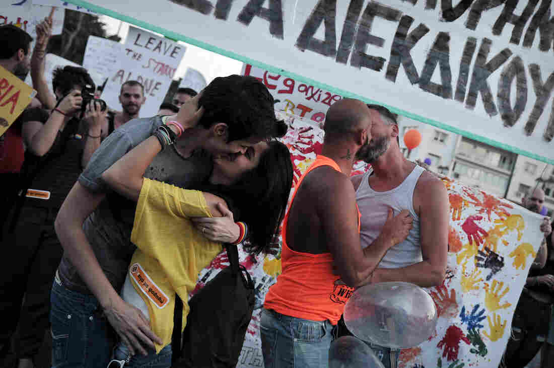 """Couples kiss during the Athens gay pride parade last June. Last month, activists organized a """"kiss-in"""" during a church service run by a Greek Orthodox bishop who has threatened to excommunicate politicians supporting same-sex unions."""