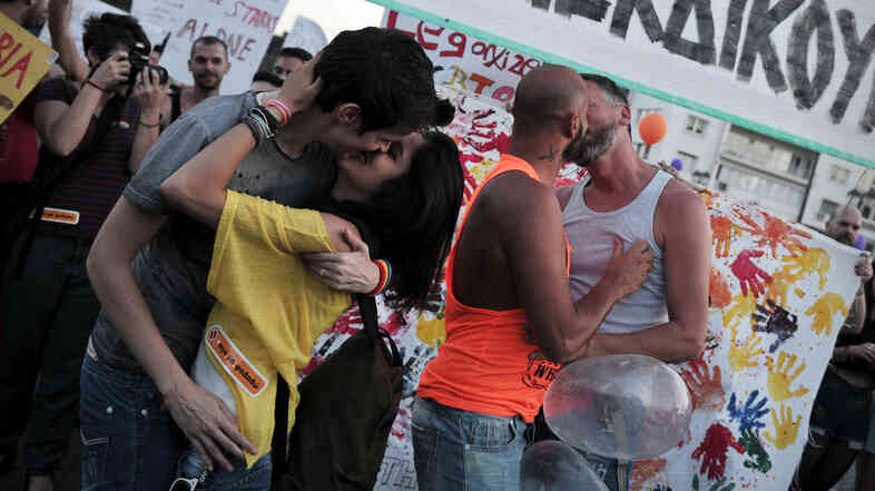 "Couples kiss during the Athens gay pride parade last June. Last month, activists organized a ""kiss-in"" during a church service run by a Greek Orthodox bishop who has threatened to excommunicate politicians supporting same-sex unions."