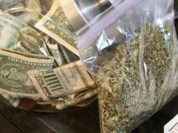 A bag of marijuana being prepared for sale sits next to a money jar at BotanaCare in Northglenn, Colorado, in this file photo taken on De