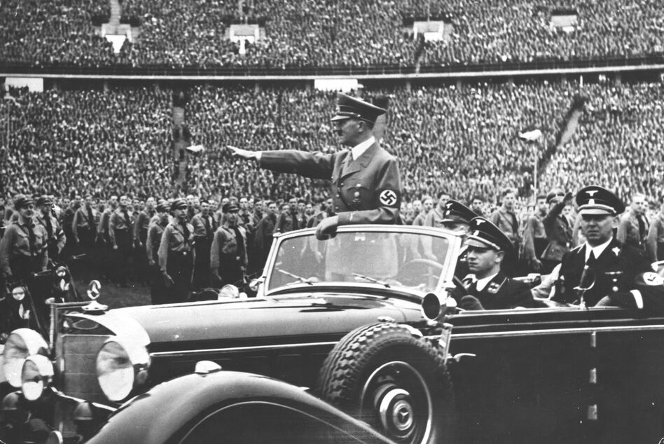 Adolf Hitler salutes to a crowd of soldiers at a Nazi rally in 1938. Years later, in the final months of World War II, the United States undertook an enormous effort to attract Nazi scientists. (Topical Press Agency/Getty Images)