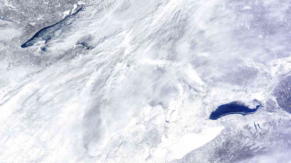 They're down there somewhere: The Great Lakes as seen from space on Wednesday. Lake Ontario, which has less ice than the others, is at the lower right. A bit of open water can be seen in Lake Superior, at the upper left