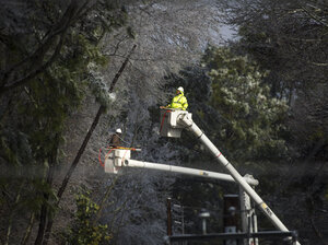 Multiple crews work to restore power after a winter storm on Thursday that brought down