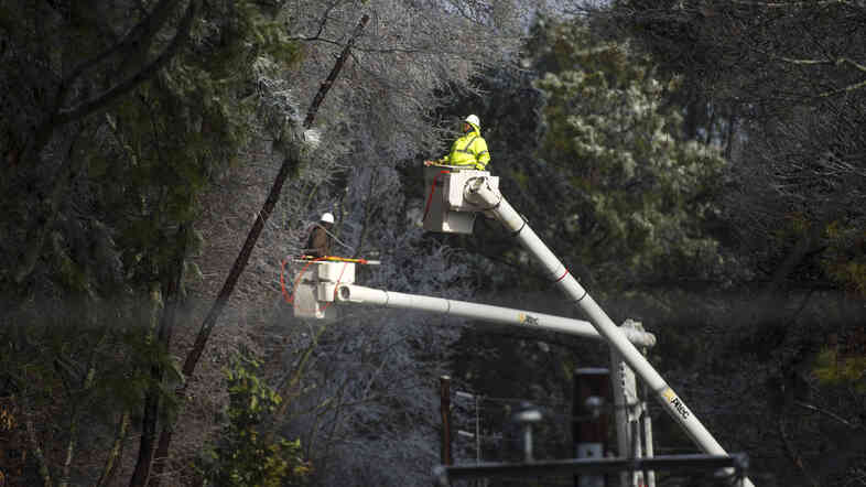 Multiple crews work to restore power after a winter storm on Thursday that brought down lines in Fairburn, Ga. Fr