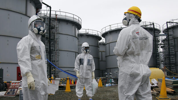 A Tokyo Electric Power Company official (center) stands with journalists at the Fukushima Dai-ichi nuclear power plant in Japan on Nov. 7. Cleanup efforts at the plant remain ongoing. (AFP/Getty Images)