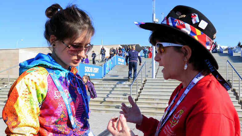 International Sports Chaplain Myrna Gregory (right) uses a souvenir pin to tell a gospel story to a Russian volunteer at the Sochi Olympic Park.