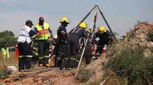 Rescue services and emergency personal try to free miners trapped underground in Benoni, east of Johannesburg, South Africa, on Sunday.