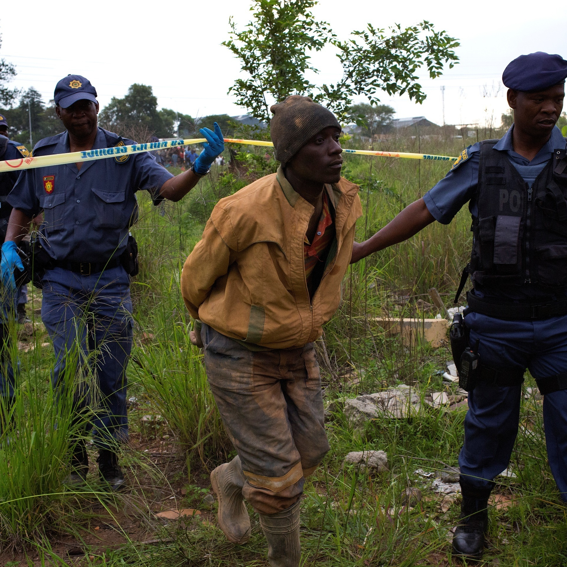 An illegal miner is led away after being arrested near Johannesburg last month. Unauthorized mining is common in the region.