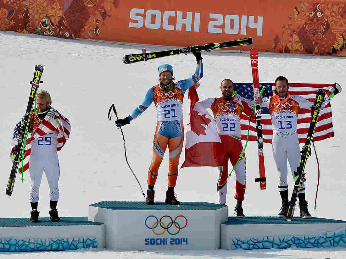 Silver medalist Andrew Weibrecht of the United States, gold medalist Kjetil Jansrud of Norway and bronze medalists Jan Hudec of Canada and Bode Miller of the United States celebrate on the podium during the flower ceremony for the Alpine Skiing Men's Super-G.