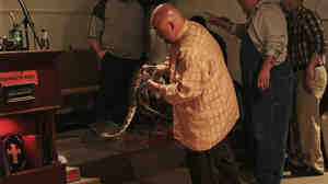 Pastor Jamie Coots holds a snake at Full Gospel Tabernacle in Jesus Name Church of Middlesboro, Ky. He died on Sunday after being bitten by a snake.