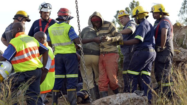 Rescuers tend to a mine worker, in striped top, after he was pulled from an illegal gold mine Sunday in Benoni, outside Johannesburg, South Afric