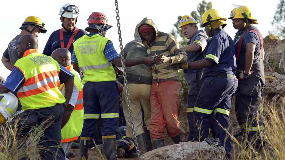 Rescuers tend to a mine worker, in striped top, after he was pulled from an illegal gold mine Sunday in Benoni, outside Johannesburg, South Africa. Many of his colleagues remain below ground