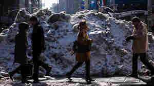 It will melt eventually: People walk past a pile of dirty snow in New York City's Times Square.
