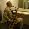 Fred Ho practices his baritone saxophone in a dressing room before a performance.