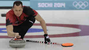 """Canada's E.J. Harnden delivers the rock during a curling training session in Sochi. """"We like to think of ourselves as athletes now and not just curlers,"""" he says."""