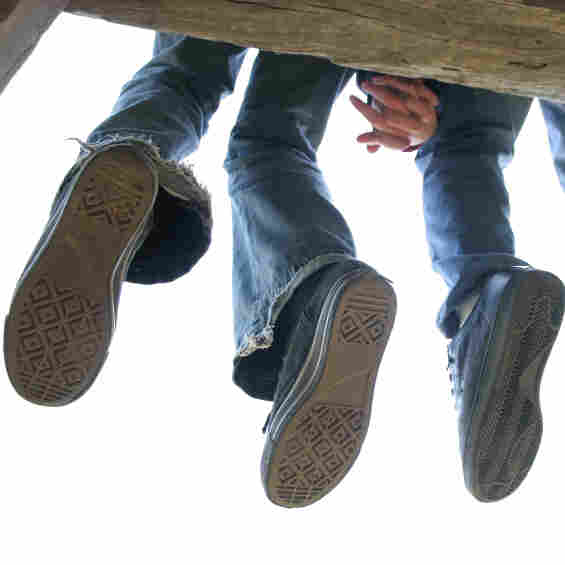 The feet of a teen couple dangle as they sit on a dock.