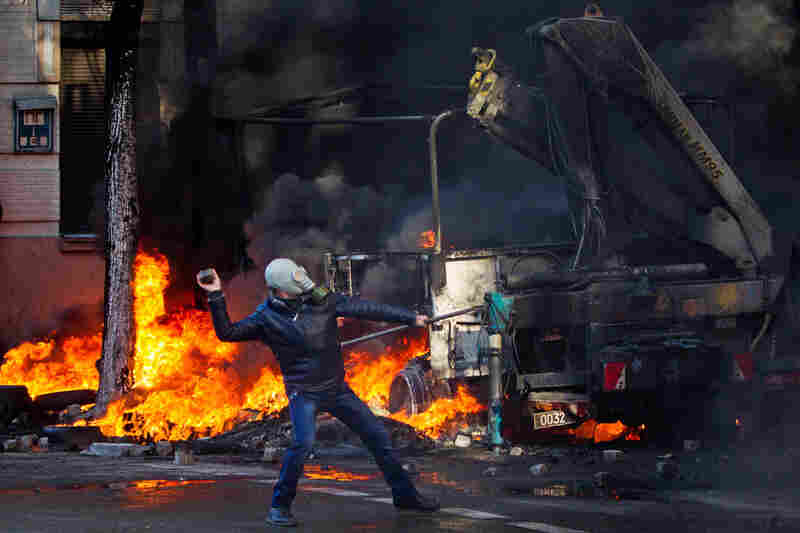 A demonstrator throws rocks during violent clashes between opposition protesters and riot police in Kiev.